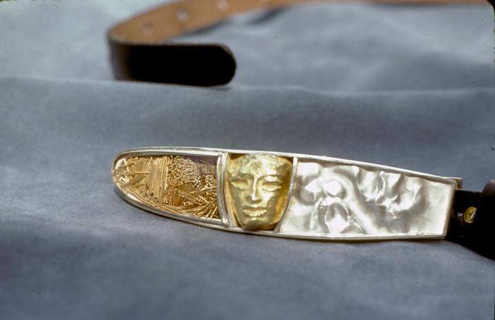 Toza, belt buckle, silver and gold with face and eyeglass lens, 1970s