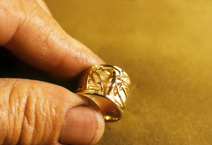 Toza holding gold ring with relief design, 1960s